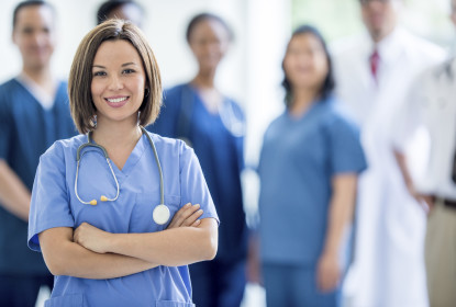 A nurse standing with her arms crossed smiling and looking at the camera; behind her a multi-ethnic group of medical professionals stand together in a hospital building.